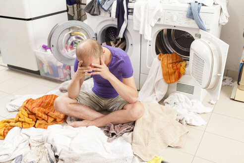 Young man sitting between dirty laundry - JUNF000412