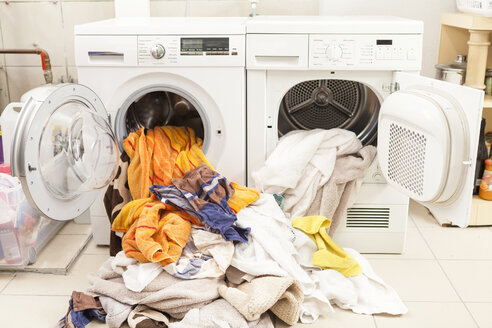 Dirty laundry flowing out of washing machine and tumble dryer - JUNF000415