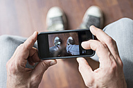 Man photographing his shoes with smartphone - ONF000844