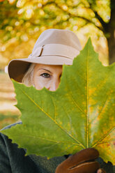 Woman wearing hat hiding behind an autumn leaf - CHAF001126