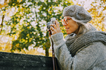 Woman taking pictures with an old camera in an autumnal park - CHAF001131
