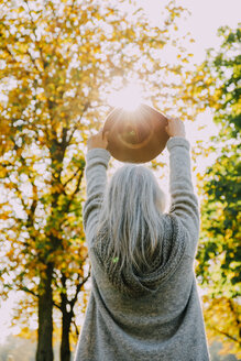 Back view of woman holding hat against the sun in an autumnal park - CHAF001134