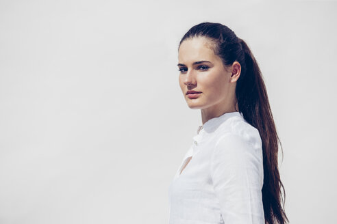 Portrait of young woman with ponytail wearing white blouse in front of white background - CHAF001216