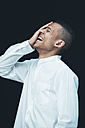 Laughing young woman with hand on his face wearing white shirt in front of black background - CHAF001240