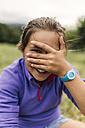 Portrait of girl peeking through her fingers - MGOF000411