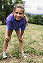 Portrait of girl standing on a meadow looking at viewer - MGOF000415
