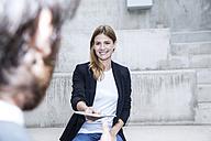 Portrait of smiling businesswoman giving digital tablet to her partner - FMKF001751