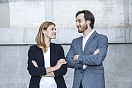 Two business people standing face to face with crossed arms - FMKF001754