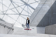 Businesswoman with pink skateboard in modern architecture - FMKF001735