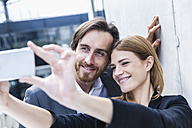 Portrait of two business people taking a selfie with smartphone - FMKF001741