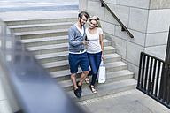 Germany, Cologne, young couple looking at smartphone walking downstairs - FMKF001756
