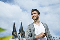 Germany, Cologne, portrait of young man with smartphone hearing music - FMKF001759