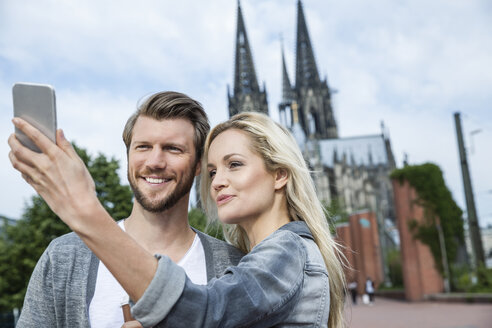 Germany, Cologne, young couple taking a selfie with smartphone - FMKF001762