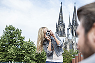 Germany, Cologne, young woman taking a picture of her boyfriend - FMKF001764