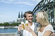 Germany, Cologne, happy young couple toasting with Koelsch glasses in front of Rhine River - FMKF001770