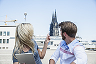Germany, Cologne, young couple with digital tablet looking at Cologne Cathedral - FMKF001781