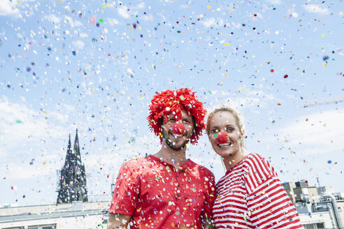 Germany, Cologne, young couple celebrating carnival dressed up as clowns - FMKF001787
