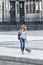 Germany, Cologne, young woman walking with her little dog in front of Cologne Cathredral - FMKF001838