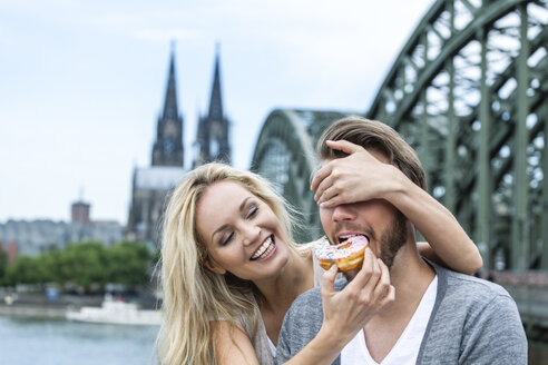 Germany, Cologne, young man tasting a bagel while his girlfriend covering his eyes - FMKF001792