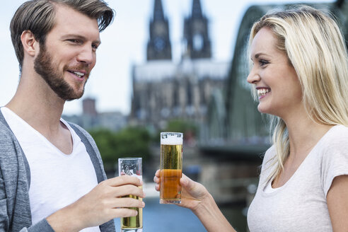 Germany, Cologne, happy young couple with Koelsch glasses - FMKF001800