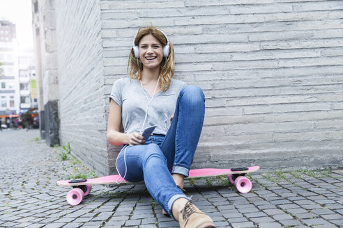 Germany, Cologne, young woman sitting on  pink skateboard hearing music with headphones - FMKF001823