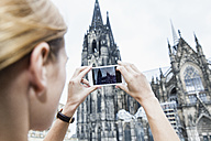Germany, Cologne, young woman taking a picture of Cologne Cathedral with smartphone - FMKF001807