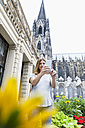Germany, Cologne, young woman taking a selfie with smartphone in front of Cologne Cathedral - FMKF001824