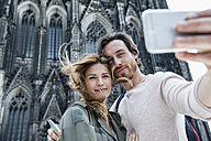 Germany, Cologne, portrait of young couple taking a selfie in front of Cologne Cathedral - FMKF001827