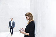 Young businesswoman leaning on concrete wall using digital tablet - FMKF001835