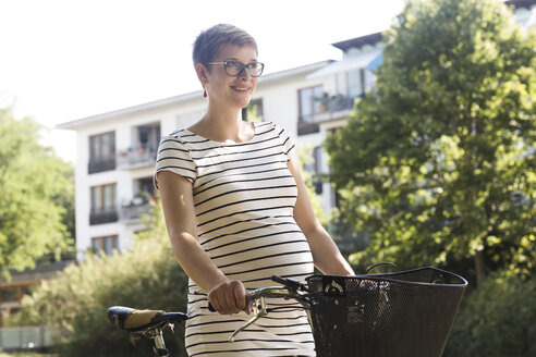 Portrait of smiling pregnant woman with bicycle - SGF001837