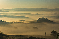 Italy, Tuscany, San Quirico d'Orcia, view to rolling landscape at sunrise in the fog - LOMF000039