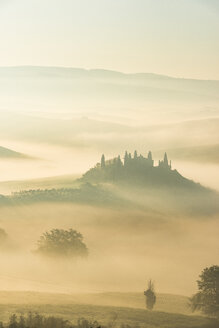 Italy, Tuscany, San Quirico d'Orcia, view to rolling landscape at sunrise in the fog - LOMF000036