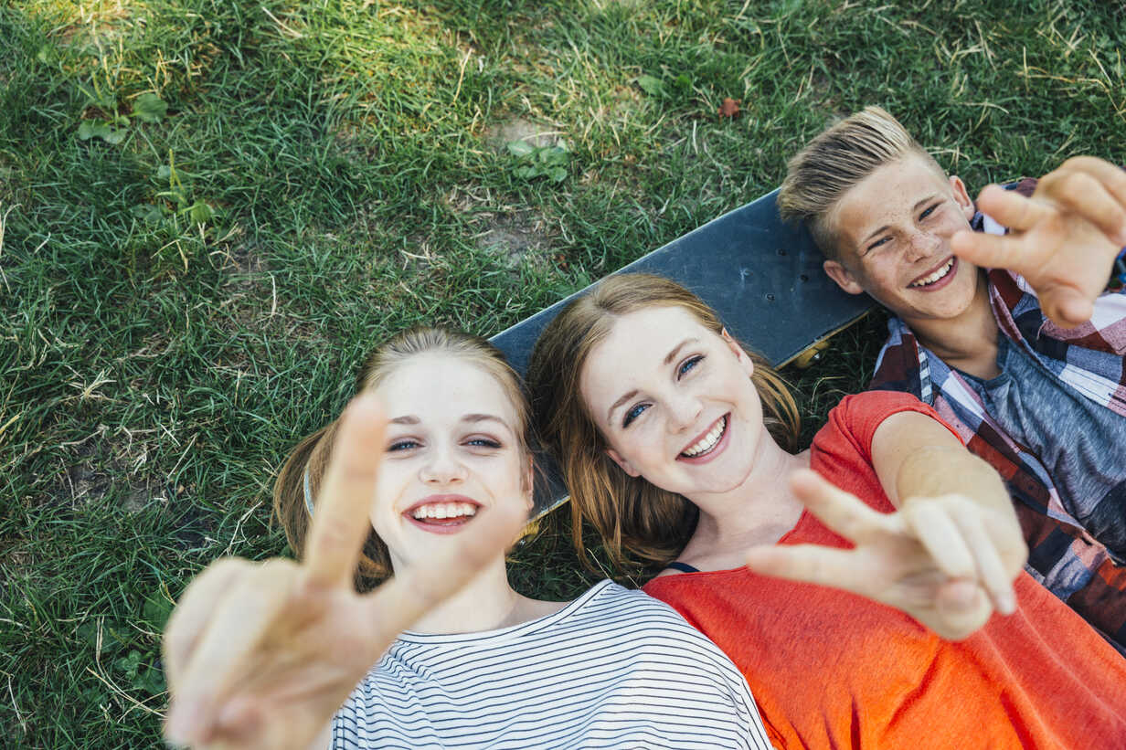 Three happy teenage friends lying on skateboard in meadow making victory sign - AIF000072 - AustrianImages/Westend61