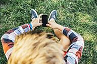Teenage boy sitting on meadow with smartphone - AIF000084