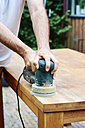 Man sanding an oak table with a random orbital sander - HAWF000823