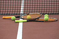 Two tennis rackets and four balls lying on ground of tennis court - MGOF000447