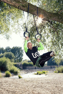 Man doing CrossFit exercise on rings hanging on tree trunk - MAEF010853