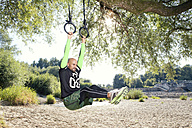 Man doing CrossFit exercise on rings hanging on tree trunk - MAEF010855