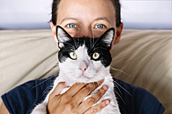 Blue eyed woman holding a black and white cat - GEMF000307