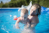 Mother with baby in swimming pool - RAEF000289
