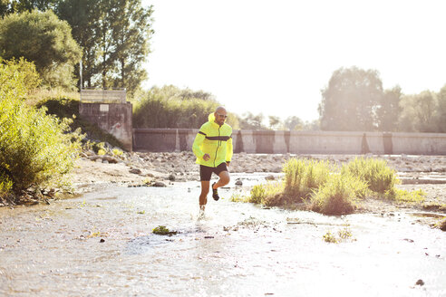 Man in sports wear running in water - MAEF010862