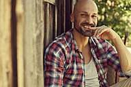 Portrait of smiling man wearing checked shirt sitting in front of wooden hut - MAEF010924