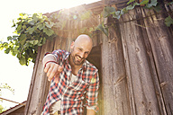 Smiling man standing in front of wooden hut poiting at viewer - MAEF010933