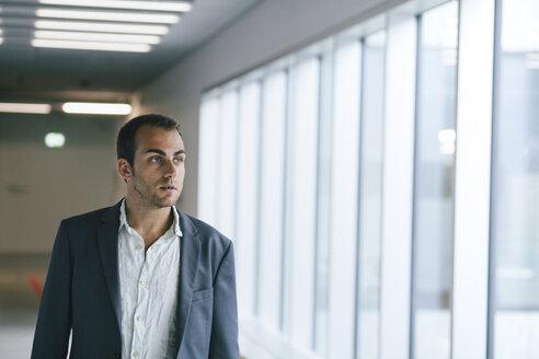 Portrait of businessman looking through window - BZF000182