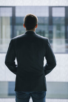 Back view of businessman looking through window - BZF000184