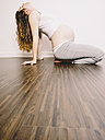 Pregnant woman on wooden floor leaning back - KRPF001623