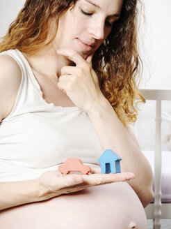 Pregnant woman in front of cot with toy house and toy car in her hand - KRPF001609