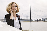 Young woman on cell phone at the riverside - STKF001377