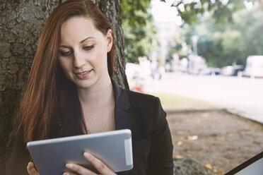 Young woman at tree looking at digital tablet - STKF001389