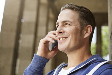 Smiling man outdoors on cell phone - STKF001392